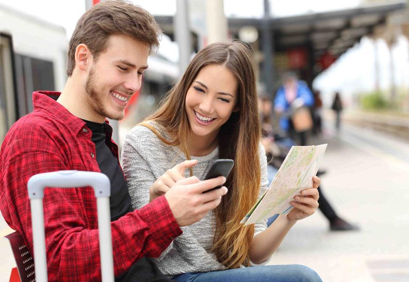 楽しそうにスマートフォンを見るカップル